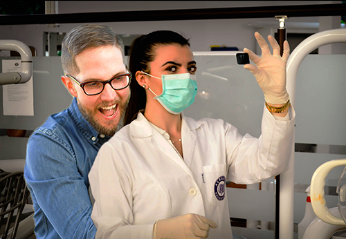 A man is hugging a female scientist from behind as she holds a sample, she looks at him, annoyed.